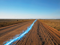 Blue streak of light on dirt road against clear sky