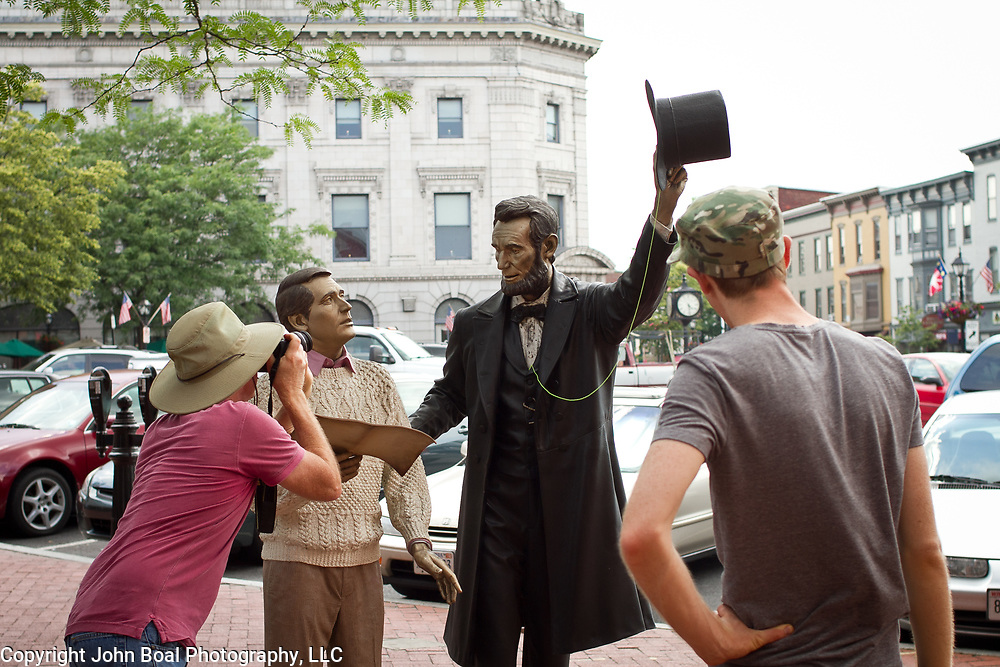 Tourists take pictures of the Abraham Lincoln statue in downtown Gettysburg, PA, during the Sesquicentennial Anniversary of the Battle of Gettysburg, Pennsylvania on Sunday, June 30, 2013.  A pivotal battle in the Civil War, over 50,000 soldiers died in the battle which spanned 3 days from July 1-3, 1863.  Later that year, President Abraham Lincoln returned to Gettysburg to deliver his now famous Gettysburg Address to dedicate the cemetery there for the Union soldiers who died in battle.  John Boal photography