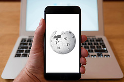 Using iPhone smartphone to display logo of Wikipedia the online encyclopaedia