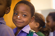 A close up of a boy with a sticker after getting weighed and evaluated at a Save the Children project. Cape Town, South Africa.