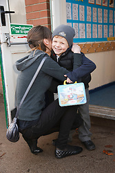 Teenage sister taking young brother to primary school