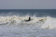 Surfer collapsing in the tide at the Marconi Beach, Cape Cod, Massachusetts, USA, September 3, 2011.