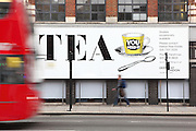 Red London bus passing through the TEA building with white display advertising for TEA, Shoreditch, London, UK. Picture by Manuel Cohen