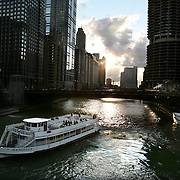 Chicago skyline along the Chicago River with sightseeing boats.<br /> Jose More Photography