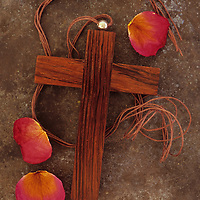 Small wooden crucifix with neck cord lying on tarnished metal with three dried deep pink rose petals