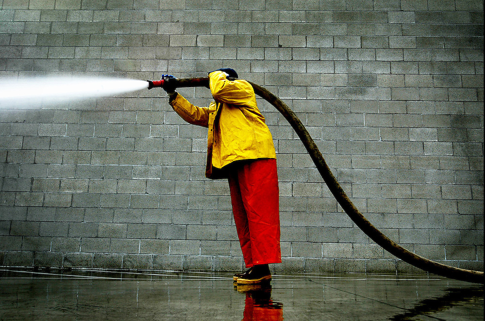 03/25/2005 - Laborer, Ron Mouse, hoses down the large concrete receiving area of the Wapato Jail, located at 10355 N. Bybee Lake Court. The jail sits unoccupied in north Portland.<br /> <br /> keywords : multnomah county prison, wapato, north portland, news 2005.