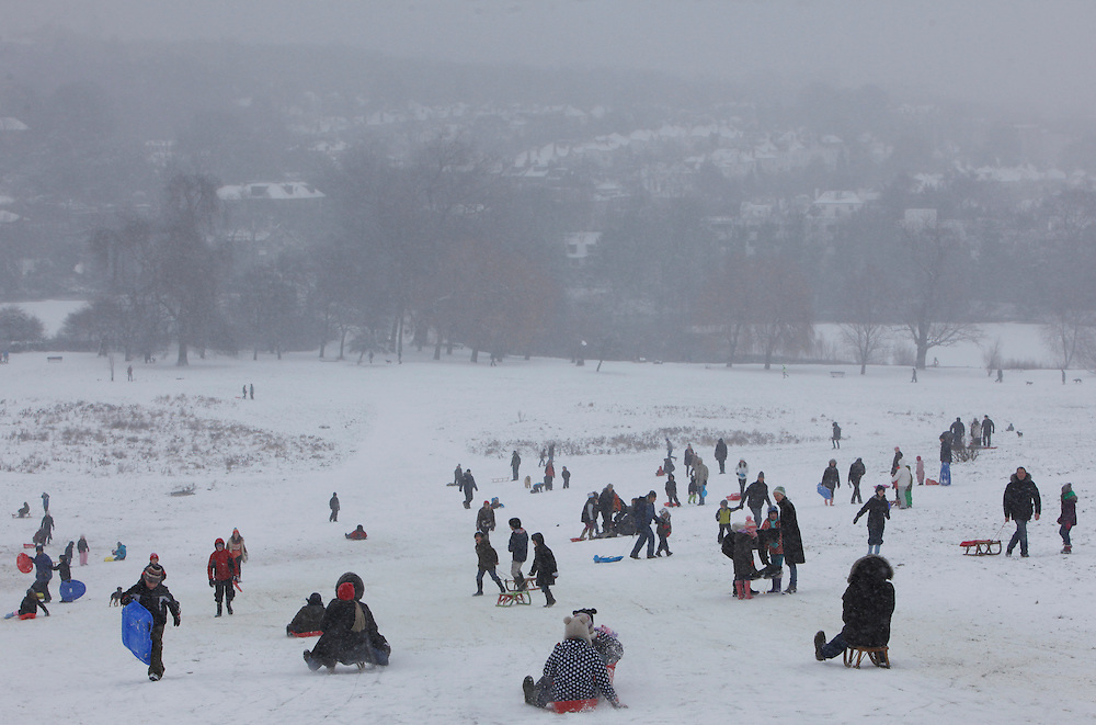 As snow falls across the capital, Londoners spend their Sunday tobogganing down Parliament Hill on Hampstead Heath. London..Sunday 20th January 2013
