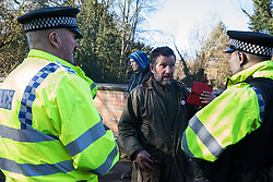 Denham, UK. 6 February, 2020. Police officers move on Mark Keir, an environmental activist from Save the Colne Valley, who was walking at a snail's pace along a road in order to block a security vehicle and truck delivering fencing and other supplies to be used for works associated with the HS2 high-speed rail link close to the river Colne at Denham Ford. Works planned in the immediate vicinity include the felling of trees and the construction of a Bailey bridge, compounds and fencing, some of which in a wetland nature reserve forming part of a Site of Metropolitan Importance for Nature Conservation (SMI).