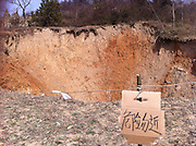 GUANGYUAN, CHINA - FEBRUARY 28: (CHINA OUT) <br /> <br /> Land-surface Collapses In Guangyuan<br /> <br /> People stand next to a pit at a village in Guangyuan, Sichuan province of China. The 24.9 metre diametre pit was formed on a karst landform last year after a ground surface kept sinking for six days in September. It is said that the pit may face further sinking after rains due to its geological conditions.  <br /> ©ChinaFoto/Exclusivepix