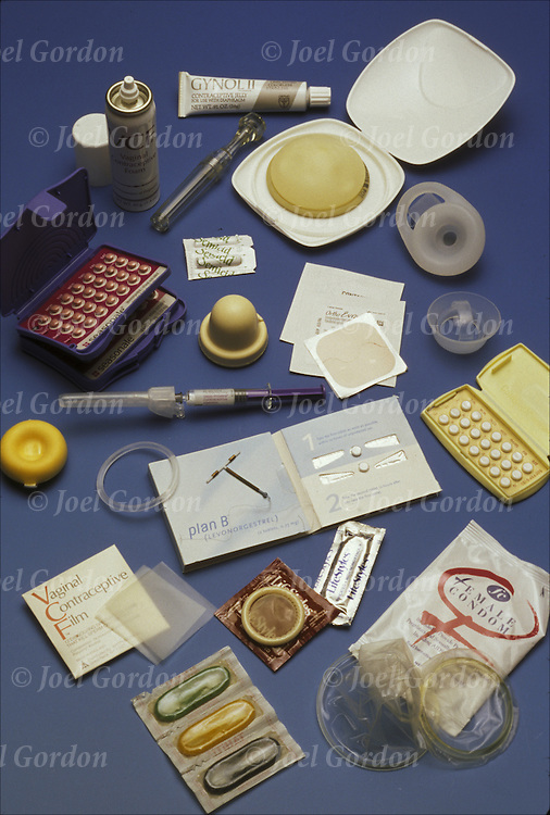 Group photo of variety of contraceptives, birth control devices: male condoms, Patch, Copper-T IUD, VCF, female condom, Cervical cap, Seasonale, Diaphragm, Jelly, Plan B, Nura Ring, Oral contraceptives, Spermicide,
