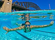 Underwater split level view of a swimmer in a North Sydney harbour bridge pool. Sydney. Australia.