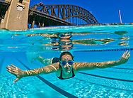 Underwater split level view of a swimmer in a North Sydney harbour bridge pool. Sydney. Australia.