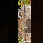 A glimpse through a door way to a courtyard and balcony -- a traditional scene in the Old City of Aleppo, Syr
