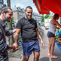 Nederland, Amsterdam, 23 juli 2016.<br />We volgen de Syrische jongen Ibrahim Najjar in de Spaarndammerbuurt in zijn zoektocht naar de ingredienten voor het Syrische kipgerecht Mskhan, een Syrisch ovengerecht met kip, citroen en ui.<br />Hij heeft zijn buren uitgenodigd bij hem te komen eten.<br />Op de foto: Ibrahim maakt een praatje met de Turkse eigenaar van kruidenier Kardeslar Market in de Spaarndammerstraat.<br /><br /><br /><br /><br />Foto: Jean-Pierre Jans