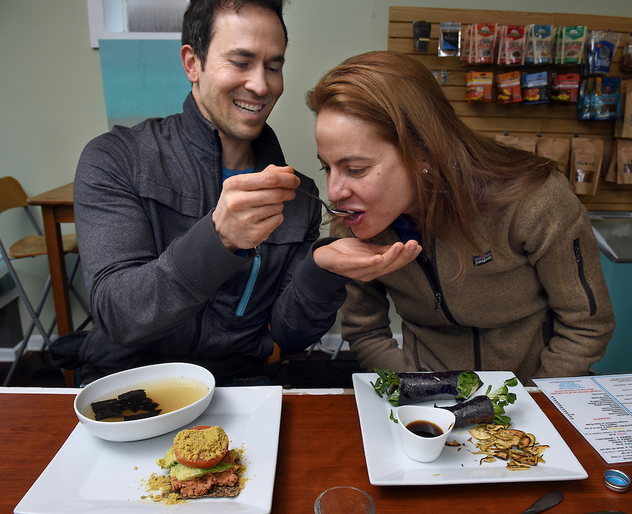 Mara Lavitt /For Hearst Connecticut Media<br /> February 6, 2016<br /> Catch A Healthy Habit Cafe, Fairfield. Robert Petrucci of Norwalk, left, gives Ann Kokkinos of Norwalk a taste of his miso soup. On his plate is a tomavo made of nut pate, tomato, avocado, on onion &quot;bread&quot; of ground flaxseed, ground sunflower seed, pureed onions and olive oil with Rawmesan (a commercial product of walnuts, sunflower seeds, nutritional yeast and salt); on her plate is a nori wrap: nori, fig marmalade, cashew &quot;cheese,&quot; beet, sunflower sprouts, avocado, crispy onion, spinach, &quot;salt &amp; vinegar&quot; zucchini chips all with a dipping sauce.