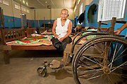 26 JUNE 2006 - SIEM REAP, CAMBODIA: SUM KHAT, 64, sits in her dorm room at Handicapped International in Siem Reap. She was walking through the jungle collecting firewood in 1983, during one of the civil wars that consumed Cambodia after the Vietnam war, when she stepped on a small plastic landmine and blew off her foot. Handicapped International helps Cambodians maimed by mines and unexploded ordinance as well as traffic accidents and disease adjust to a life without limbs. Cambodians are still wrestling with the legacy of the war in Vietnam and subsequent civil wars. At one time it was the most heavily mined country in the world and a vast swath of Cambodia, along the Thai-Cambodian border, is still mined. In 2004, more than 800 people were killed by mines and unexploded ordinance still found in the countryside.  Photo by Jack Kurtz