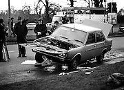 Members of the Garda Technical Squad examine the Fiat 131 that was being driven by Dr Jim Donovan when a bomb planted in the car exploded. Dr Donovan, Senior Forensic Scientist with the Garda Technical Bureau, was critically injured in the explosion at Newlands Cross, County Dublin. The bomb is believed to have been the work of Dublin criminal Martin Cahill, 'The General', as Dr Donovan was due to testify against him in an armed robbery case.<br />