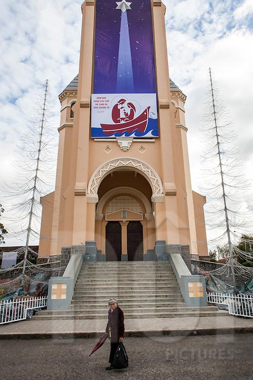A woman walks along the facade of Cock Church, Da Lat, Vietnam, Southeast Asia