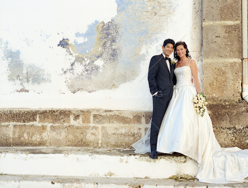 Bride and groom standing by a plaster colored wall in Italy