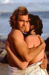 shirtless couple embracing on the beach
