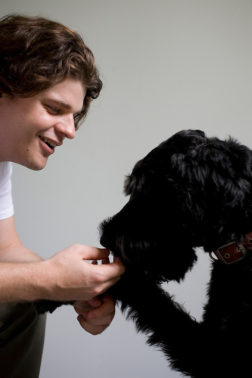 Prof. Brian Hare, Director of the Duke Canine Cognition lab, with a test subject, Henry, a Giant Schnoodle, on the campus of Duke University in Durham, N.C., Monday, June 15, 2009.