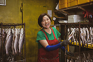 Busan, South Korea - September 17, 2019: A woman with a warm smile works with fish at the Jagalchi Market in Busan, South Korea.