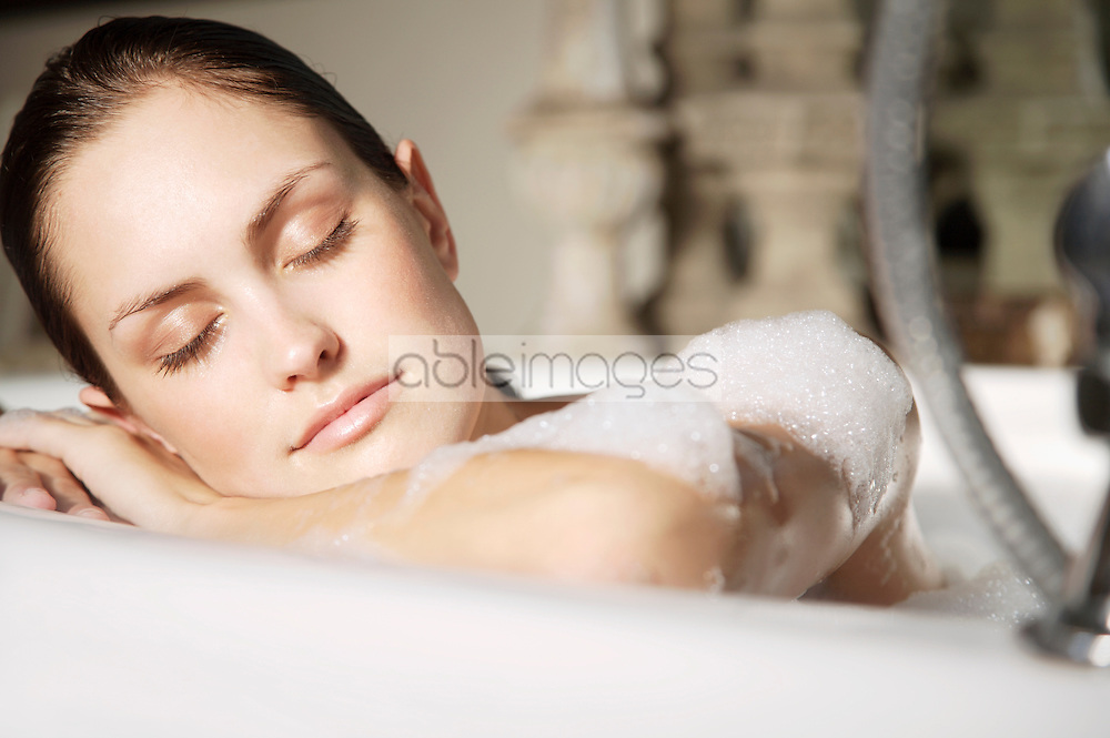 Close up  of a young woman relaxing her head against edge of bathtub