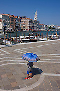 A boy carries a Venice picture umbrella in front of Santa Maria della Salute church in Dorsoduro, overlooking the Grand Canal and San Marco district.