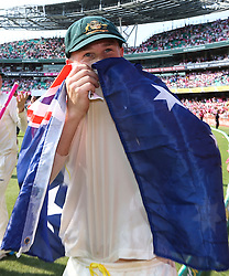 © Licensed to London News Pictures. 05/01/2014. David Warner kisses the crest on his shirt while wearing the Australian flag during celebration lap during day 3 of the 5th Ashes Test Match between Australia Vs England at the SCG on 5 January, 2013 in Melbourne, Australia. Photo credit : Asanka Brendon Ratnayake/LNP