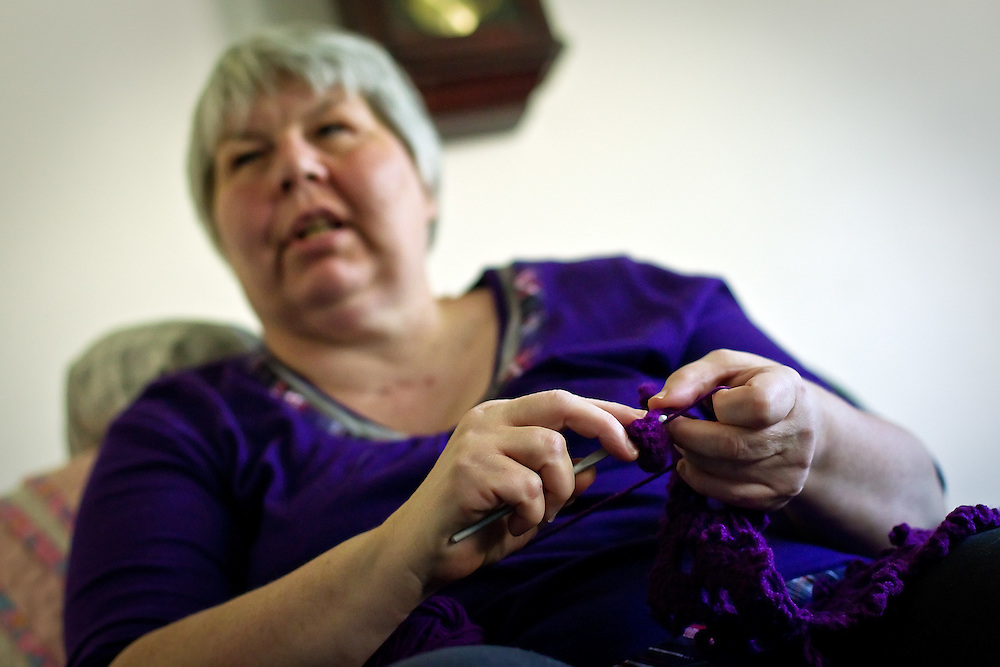 DeLaine Mardell works her crocheting needle through fabric as she crafts an item in her living room.