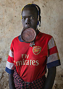 The football stars of tomorrow<br /><br />Thousands of Football shirts of Arsenal, Manchester, Chelsea, Milano, etc end up their carreer in... Ethiopia. Sold in the deep south, in the Omo Valley, those second hand clothes are bought by the local tribes. Most of them ignore the meaning of those shirts, and just buy them for the color, the logo, or the shape.<br />No warrior will go out without his little pillow/seat.<br />Some, like in Hamer tribe wear at the top of the head a clay helmet where they can put some ostrich feathers when they make a special action, like killing a wild animal, or...a man.<br />Those tribes won't exist in few years as the ethiopian governement has launched a huge plan to develop the area.<br />Soon, a highway coming from Mombassa - Nairobi will pass thru the villages to reach Addis Ababa.<br /><br />Photo shows: Mursi Tribe - Arsenal<br />©Eric Lafforgue/Exclusivepix Media
