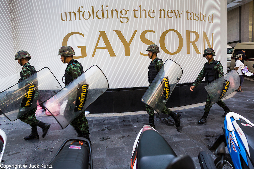 "01 JUNE 2014 - BANGKOK, THAILAND: Thai troops move into position at Gaysorn, a high end shopping mall in Bangkok. The Thai army seized power in a coup that unseated a democratically elected government on May 22. Since then there have been sporadic protests against the coup. The protests Sunday were the largest in several days and seemed to be spontaneous ""flash mobs"" that appeared at shopping centers in Bangkok and then broke up when soldiers arrived. Protest against the coup is illegal and the junta has threatened to arrest anyone who protests the coup. There was a massive security operation in Bangkok Sunday that shut down several shopping areas to prevent the protests but protestors went to malls that had no military presence.    PHOTO BY JACK KURTZ"