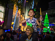 """31 DECEMBER 2012 - BANGKOK, THAILAND: A man carries his son through New Year's Eve party and countdown in Ratchaprasong Intersection in Bangkok. The traditional Thai New Year is based on the lunar calender and is celebrated in April, but the Gregorian New Year is celebrated throughout the Kingdom, especially in larger cities and tourist centers, like Bangkok, Chiang Mai and Phuket. The Bangkok Countdown 2013 event was called """"Happiness is all Around @ Ratchaprasong."""" All of the streets leading to Ratchaprasong Intersection were closed and the malls in the area stayed open throughout the evening.    PHOTO BY JACK KURTZ"""
