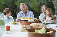 Grandparents with grandchildren (5-6) sitting at garden table