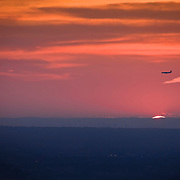 A plane lands at sunset over Queens, New York