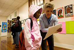 17th Jan, 2006. New Orleans, Louisiana. Post Katrina. School re-opening. A teacher helps a child find her new classroom as she starts Lusher Charter School in uptown New Orleans on their first day back since Hurricane Katrina. <br /> Photo; Charlie Varley/varleypix.com