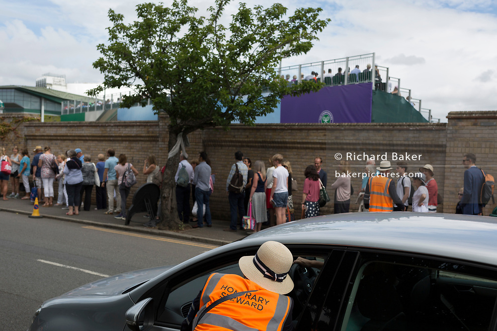 Queueing spectators wait to enter the grounds of the All England Lawn Tennis Club during the Wimbledon tennis championships, on 3rd July 2017, in Wimbledon, London, England.