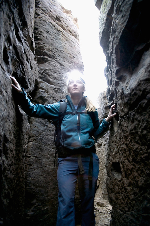 Woman hiking in a narrow passageway, Vantage, Washington USA
