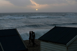 © Licensed to London News Pictures. 06/01/2014, Milford on Sea, UK. People walk on the beach as the sun set at Milford on Sea, England , Monday, Jan. 6, 2014. Part of UK continue to be affected by floods and strong wind. Photo credit : Sang Tan/LNP