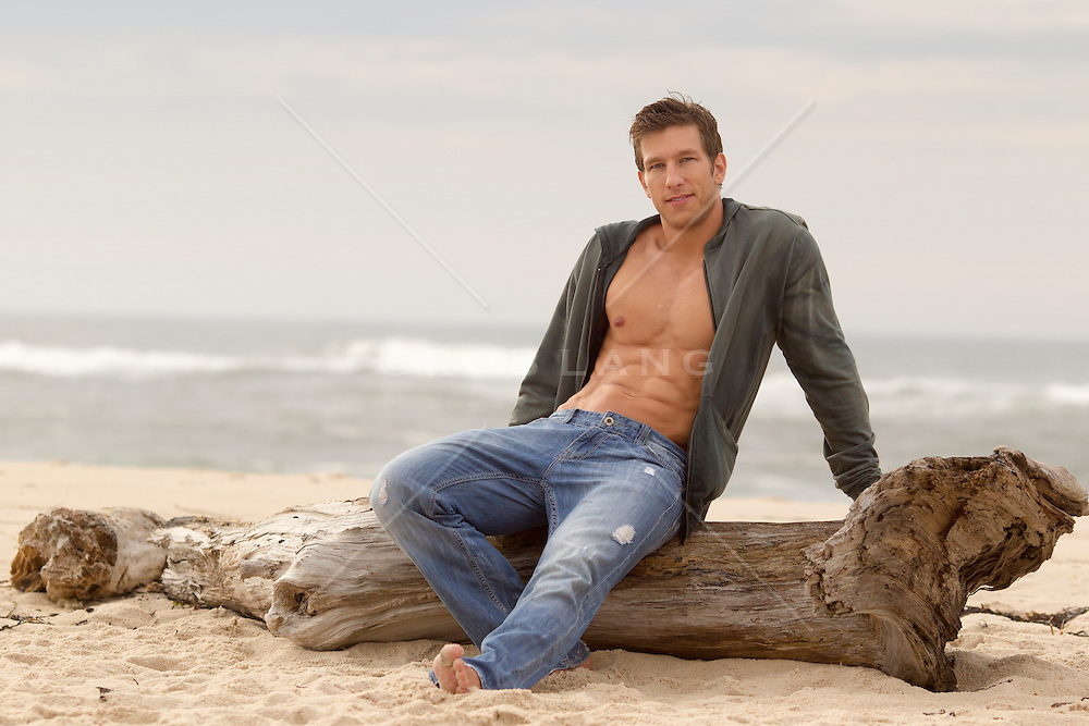 good looking man with an open shirt relaxing on washed up tree trunk at the beach in Southampton,NY