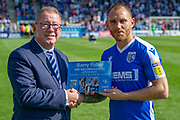 Gillingham FC defender Barry Fuller (12) receives a plaque from Gillingham chairman Paul Scally, marking 200 appearances for the club before the EFL Sky Bet League 1 match between Gillingham and Wycombe Wanderers at the MEMS Priestfield Stadium, Gillingham, England on 14 September 2019.