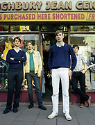 Four men standing in front of shop window.