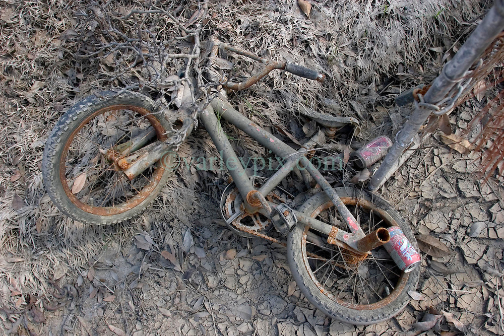 01 October, 05.  New Orleans, Louisiana. Lower 9th ward. Hurricane Katrina aftermath. <br /> The remnants of the lives of ordinary folks, now covered in mud as the flood waters recede. A child's bicycle lies in the drying mud.<br /> Photo; ©Charlie Varley/varleypix.com