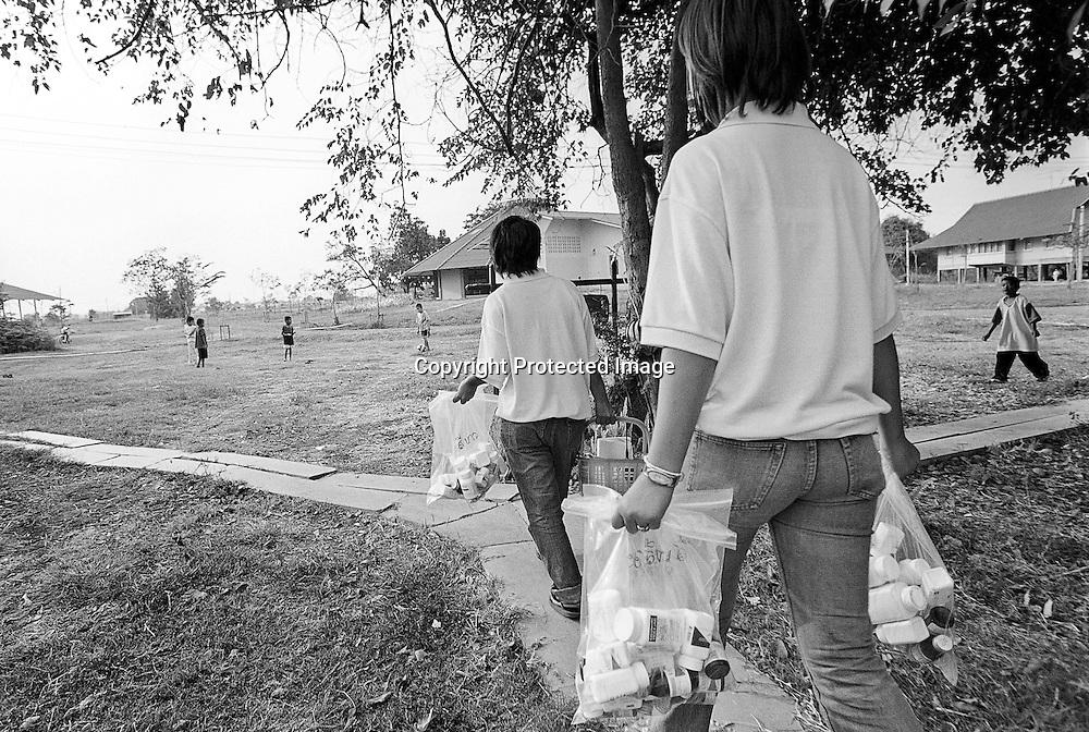 Die Krankenschwestern Re und Gai haben die woechentliche Medizin in Tueten abgepackt und bringen diese zu den einzelnen Hauesern. Die Kinder spielen im Hintergrund auf der Wiese..Provinz Lop Buri, Thailand......