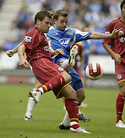 Photo: Aidan Ellis.<br /> Wigan Athletic v Reading. The Barclays Premiership. 26/08/2006.<br /> Reading's Graeme Murty (L) is challenged by Wigan's Leighton Baines