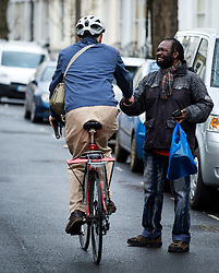 © Licensed to London News Pictures. 09/01/2016. London, UK. Labor party leader JEREMY CORBYN shakes the hand of a local resident while riding his bike, leaves his home in Islington, north London. Corbyn has come under critisism following his recent cabinet reshuffle. Photo credit: Ben Cawthra/LNP