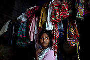 (name changed) Neelam Bharadwaj, 16, is standing among some clothes inside her family's home in Rajbhar village, located around 20 kilometres away from Varanasi, in Uttar Pradesh, India. Neelam was raped when she was 13 years old. After walking to a local shop on the main road neighbouring her village, she was forcibly picked up by two men. While one of them was raping her in the bushes, the other watched out. After some time, she managed to free herself and run away, hiding under a bridge in cold dirty water for several hours. When she returned home in the morning, the family was too afraid to go to the police, but activist Mangla Parsad, 34, from PVCHR, convinced the family to take the right action. The police initially insulted and threatened the family for bringing the facts up, but filed the official case (FIR) nevertheless. The rape was not mentioned in the file due to an inaccurate and superficial medical record that did not, in fact, mention it. Because of social shame facing by victims of rape in India, the family agreed to wed Neelam to an older man, with help of an agent. After the marriage, her husband raped her again for a whole month before she decided to return home with her family. Neelam's father works in the metal industry in Mumbai and manages to send around 2-3000 INR every month. He only visits the family once in a year. Neelam goes to school and she is studying in 11th Class Standard. She is interested in doing BA in Arts after completing her high school 12th final year.