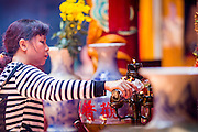 "12 APRIL 2012 - HO CHI MINH CITY, VIETNAM: A woman pours holy oil over a lamp in Quan Am Pagoda. Chùa Quan Âm (Avalokiteshvara Pagoda), a Chinese style Buddhist pagoda in Cho Lon. Founded in the 19th century, it is dedicated to the bodhisattva Quan Âm. The pagoda is very popular among both Vietnamese and Chinese Buddhists. Cholon is the Chinese-influenced section of Ho Chi Minh City (former Saigon). It is the largest ""Chinatown"" in Vietnam. Cholon consists of the western half of District 5 as well as several adjoining neighborhoods in District 6. The Vietnamese name Cholon literally means ""big"" (lon) ""market"" (cho). Incorporated in 1879 as a city 11 km from central Saigon. By the 1930s, it had expanded to the city limit of Saigon. On April 27, 1931, French colonial authorities merged the two cities to form Saigon-Cholon. In 1956, ""Cholon"" was dropped from the name and the city became known as Saigon. During the Vietnam War (called the American War by the Vietnamese), soldiers and deserters from the United States Army maintained a thriving black market in Cholon, trading in various American and especially U.S Army-issue items.          PHOTO BY JACK KURTZ"