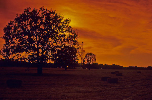 Stock photo of the silhouette of a oil and gas drilling rig in a hay field in Texas at sunset.