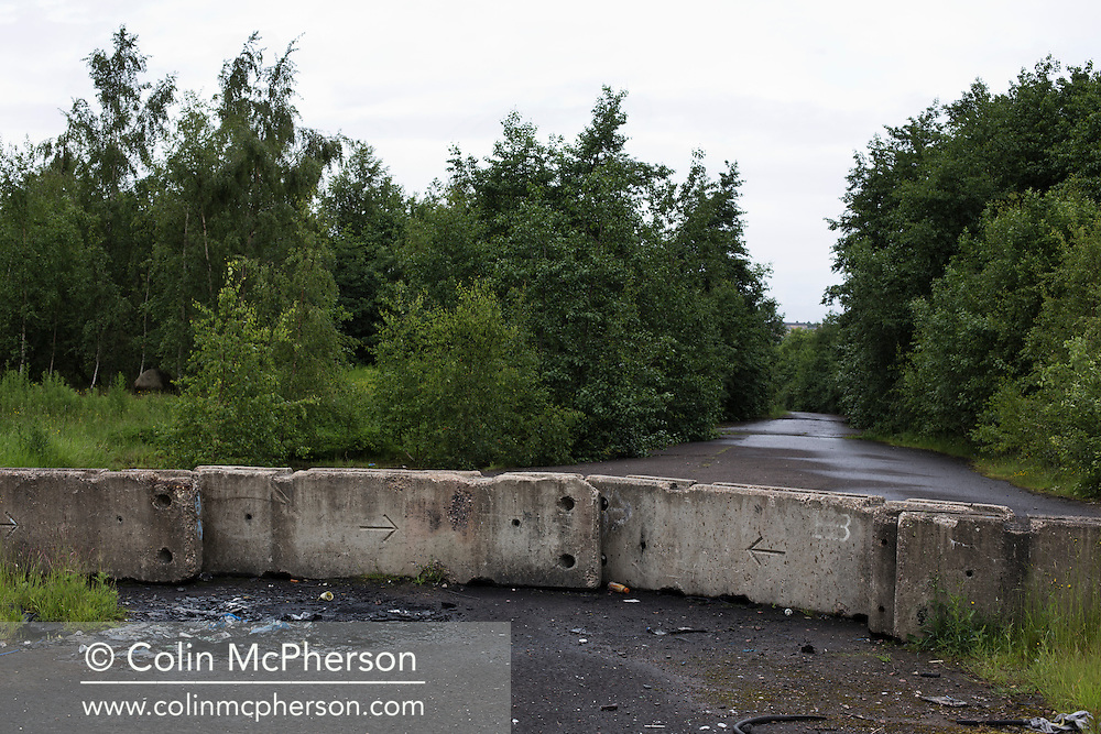 'Untitled, 2014' from the project 'The Fall and Rise of Ravenscraig' by photographer Colin McPherson.<br /> <br /> The photograph shows a road through the site of the former steelworks at Ravenscraig.<br /> <br /> This project, photographed in 2014, looks at the topography of the post-industrial landscape at Ravenscraig, the site until its closure in 1992 of the largest hot strip steel mill in western Europe. In its current state, Ravenscraig is one of the largest derelict sites in Europe measuring over 1,125 acres (4.55 km2) in size, an area equivalent to 700 football pitches or twice the size of Monaco. It is currently being developed with a mix of housing, retail and the home of South Lanarkshire College and the Ravenscraig Regional Sports Facility.